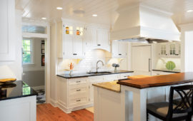 Remodeled kitchen with white cabinets and backsplash